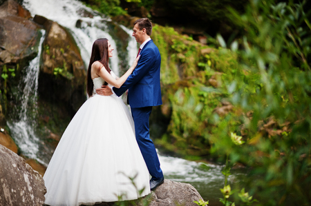 Lovely wedding couple against waterfall on sunset at Carpathian mountains. Stock Photo