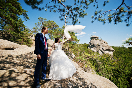 Lovely wedding couple at amazing landscapes with rock Dovbush, Carpathian mountains at Ukraine.