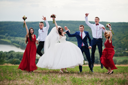 Wedding couple with bridesmaids and best mans walking outdoor. Stock Photo - 76768520