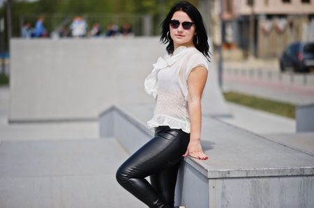 Brunette girl on womens leather pants and white blouse, sunglasses, posed against skate park.