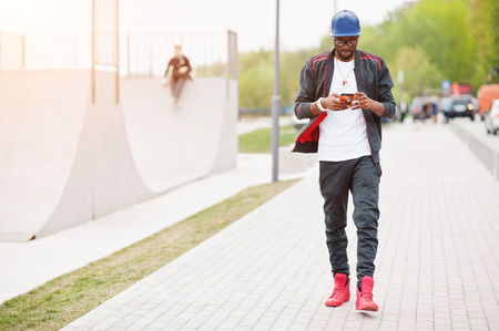 skate park: Portrait of stylish african american man on sportswear, cap and glasses looking on his phone. Black men model walk at skate park. Stock Photo
