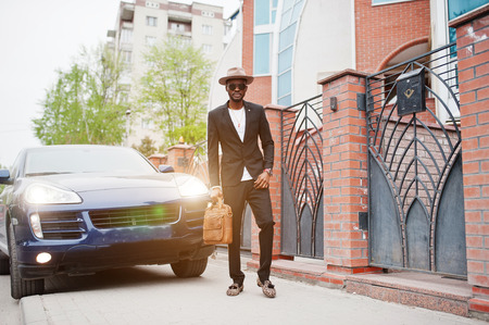 Stylish black man at glasses with hat, wear on suit with handbag against luxury car. Rich african american businessman. Stock Photo