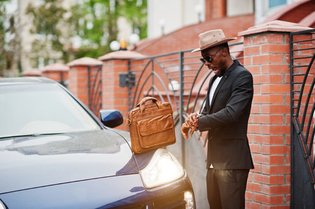 Stylish black man at glasses with hat, wear on suit with handbag against luxury car. Rich african american businessman. Late for work concept, looking at watches.