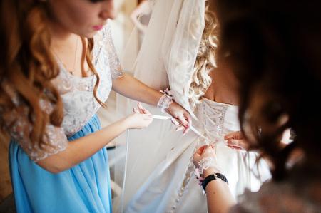 Bridesmaids and bride preparing at room on wedding morning.