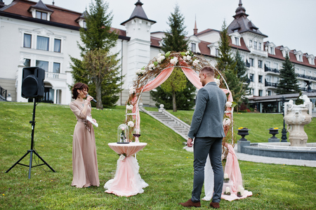 Young Fashionable Lovely Couple With Speech Master Of Wedding Ceremony Against Decor Arch On Anniversary