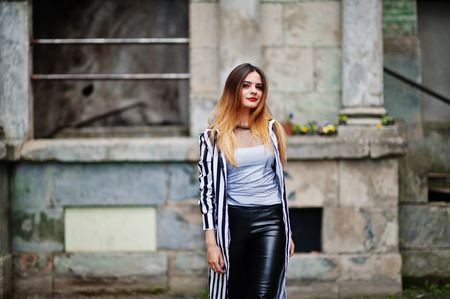 strip shirt: Fashionable woman look with black and white striped suit jacket, leather pants,  posing at old street. Concept of fashion girl.