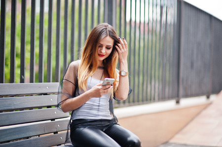 Fashionable woman look at white shirt, black transparent clothes, leather pants, posing at street and sitting on bench with cell phone. Concept of fashion girl. Stock Photo