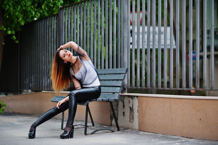 strip shirt: Fashionable woman look at white shirt, black transparent clothes, leather pants, posing at street sitting on bench against iron fence. Concept of fashion girl.