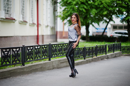 strip shirt: Fashionable woman look at white shirt, black transparent clothes, leather pants, posing at street against iron fence. Concept of fashion girl.