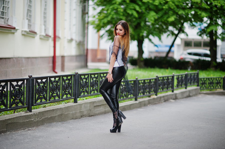 Fashionable woman look at white shirt, black transparent clothes, leather pants, posing at street against iron fence. Concept of fashion girl.