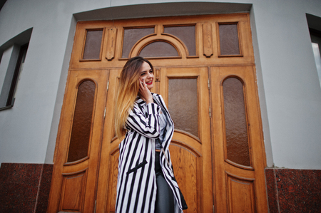 Fashionable woman look with black and white striped suit jacket, leather pants, posing against large wooden door of building and speaking on phone. Concept of fashion girl. Stock Photo