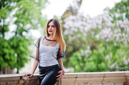 Fashionable woman look at white shirt, black transparent clothes, leather pants, posing at street. Concept of fashion girl.