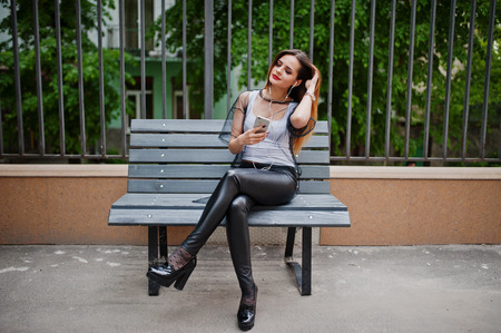 strip shirt: Fashionable woman look at white shirt, black transparent clothes, leather pants, posing at street and sitting on bench with cell phone and headphones. Concept of fashion girl listening music on mobile. Stock Photo