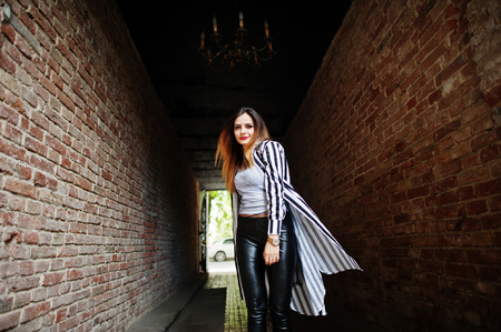 Fashionable woman look with black and white striped suit jacket, leather pants, posing at old street red brick tunnel. Concept of fashion girl.