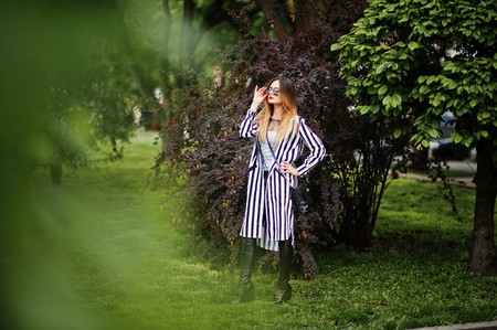 strip shirt: Fashionable woman look with black and white striped suit jacket, leather pants and sunglasses posing against bushes at street. Concept of fashion girl. Stock Photo
