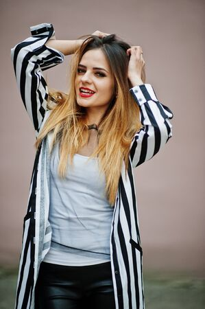 strip shirt: Close up portrait of fashionable woman look with black and white striped suit jacket, hands on hair. Emotional fashion girl.