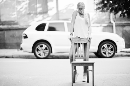 Stylish blonde woman wear at jeans, glasses, choker and white shirt near chair against luxury car. Fashion urban model portrait. Stock Photo
