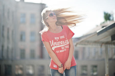Stylish happy blonde woman wear at jeans, sunglasses and t-shirt posed at street on sunny weather. Fashion urban model portrait. Stock Photo