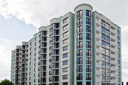 Balcony of new modern turquoise multi storey residential building house in residential area on sunny blue sky. Stock Photo