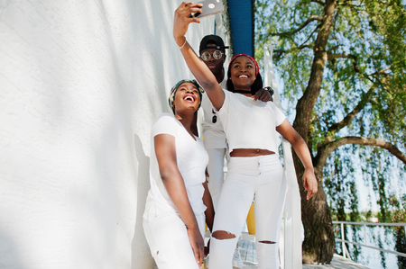 Three stylish african american friends, wear on white clothes making selfie. Street fashion of young black people. Black man with two african girls.