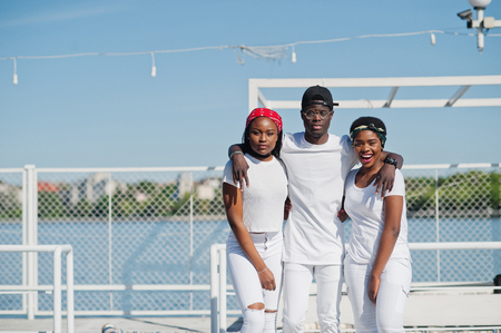 rapping: Three stylish african american friends, wear on white clothes at pier on beach. Street fashion of young black people. Black man with two african girls.