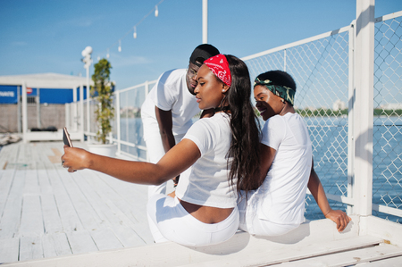 rapping: Three stylish and trendy african american people, wear on white clothes against lake on pier beach making selfie. Street fashion of young black friends.