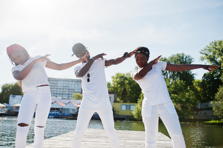 Three stylish african american friends, wear on white clothes at pier on beach showing dab. Street fashion of young black people. Black man with two african girls.