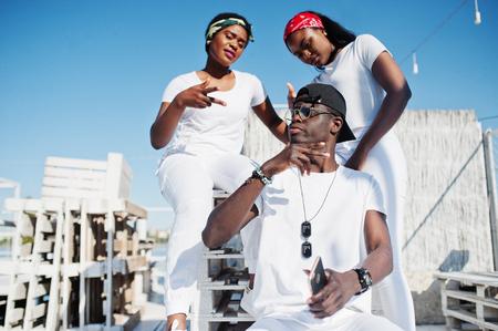 Tres amigos afroamericanos elegantes, desgaste en la ropa blanca en el embarcadero en la playa. Moda callejera de jóvenes negros. Hombre negro con dos niñas africanas.