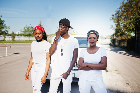 rapping: Three stylish african american friends, wear on white clothes against two luxury cars. Street fashion of young black people. Black man with two african girls.