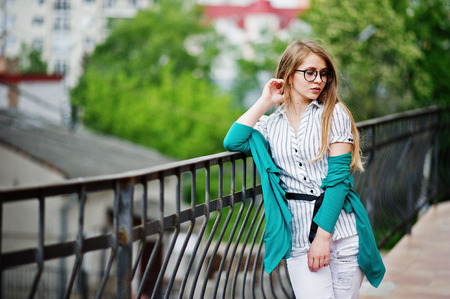 Trendy girl at glasses and ripped jeans against barrier on street.