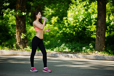 Fitness sport girl in sportswear posed at road in park and drinking water from bottle, outdoor sports, urban style.
