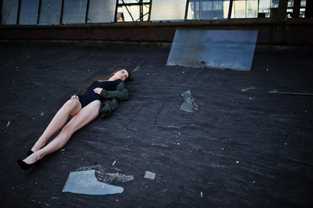 Sexy model girl wit long legs at black lingerie outfit body swimsuit combidress and jacket posed at the roof of abadoned industrial place with windows. Stock Photo