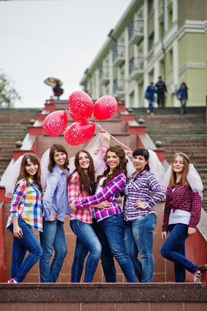 Group of six girls having fun at hen party, with balloons under rain at stairs of city.