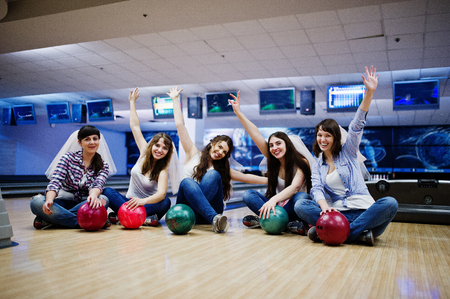rooting: Group of six girls wit bowling balls at hen party on bowling club.