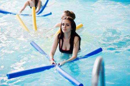 Fitness-Gruppe von Mädchen, die Aerobic-Übungen im Schwimmbad im Aquapark machen. Sport- und Freizeitaktivitäten Standard-Bild - 79876176