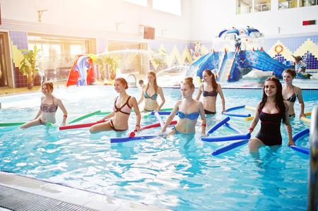 Fitness-Gruppe von Mädchen, die Aerobic-Übungen im Schwimmbad im Aquapark machen. Sport- und Freizeitaktivitäten Standard-Bild - 79877242
