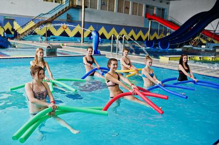 Fitness-Gruppe von Mädchen, die Aerobic-Übungen im Schwimmbad im Aquapark machen. Sport- und Freizeitaktivitäten Standard-Bild - 79812873