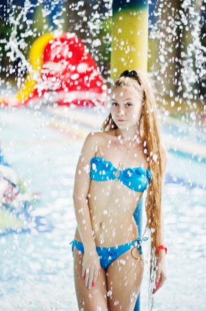 Portrait of a beautiful girl wearing blue bikini in a pool posing with the water sprinkling above her head. Stock Photo