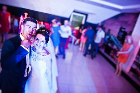 뒤에 다른 사람들과 댄스 플로어에서 행복 한 웃는 결혼식 커플의 사진을 닫습니다.