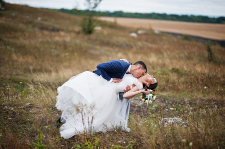 enchanting: Fantastic wedding couple walking in the tall grass with the pine trees and rocks in the background holding hands.