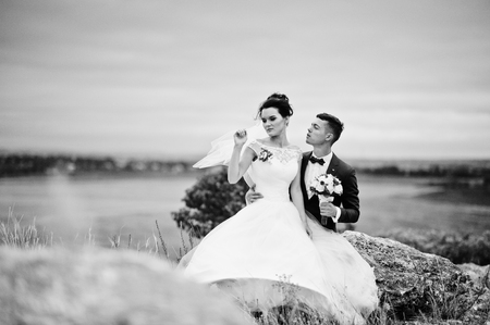 Beautiful bride and handsome groom are sitting on the stone with a beautiful landscape on the background on their wedding day. Black and white photo.