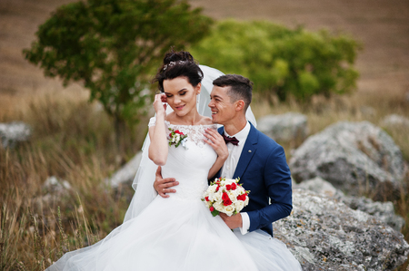 Beautiful bride and handsome groom are sitting on the stone with a beautiful landscape on the background on their wedding day.