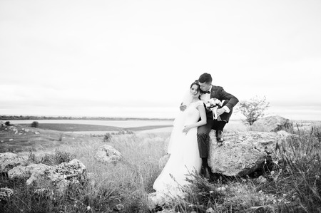enchanting: Beautiful bride and handsome groom are sitting on the stone with a beautiful landscape on the background on their wedding day. Black and white photo.