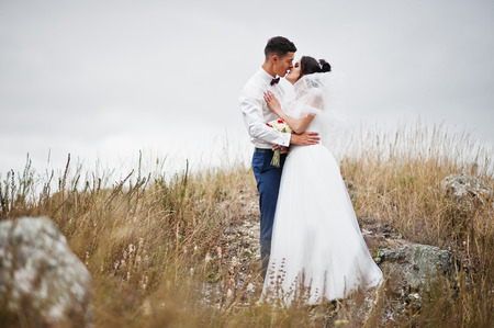 Fantastic wedding couple walking in the tall grass with the pine trees and rocks in the background holding hands.
