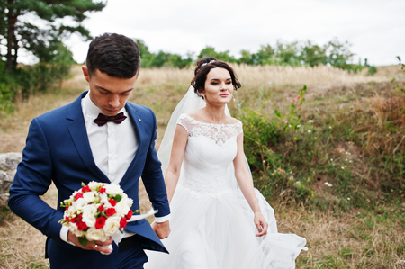 Newly married enjoy each others company in a beautiful countryside with pine trees and dry grass on a wedding day.