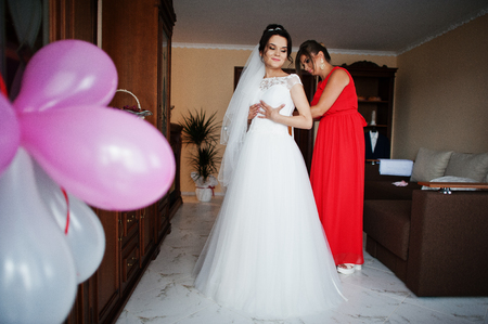 Bridesmaid helping to tie a ribbon on a wedding dress in a room with balloons in it.