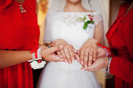 Gorgeous bride with her perfect braidsmaids in her room smiling and discussing wedding. Stock Photo