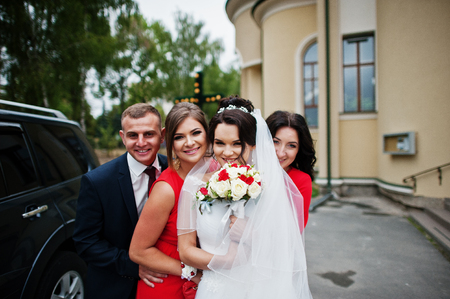 Charming bride with a groomsman and bridesmaids standing outside the church next to the luxurious wedding car. Stock Photo