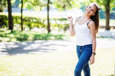 晴れた日に公園でポーズをとって素晴らしい若いモデルの女の子のクローズ アップの肖像画。