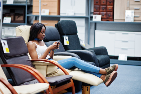 sidewalk sale: Portrait of a perfect african american woman using her smartphone in the shop.